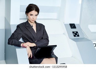 Beautiful brunette in a gray jacket in business style on a futuristic white background with a tablet and a phone in her hands. It's like a spaceship. Near black robot