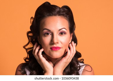 Beautiful brunette with hairdo and make up poses in studio, pin up style, close up portrait