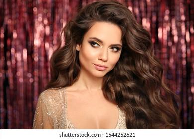 Schöne Brunette mit gesundem, gewelltem Haar. Glamour Make-up. Fashion Beauty Girl mit Karnevalmaske Einzeln auf hellem Bokeh-Hintergrund.  Gold-Schmuck-Kopienraum. Friseur.