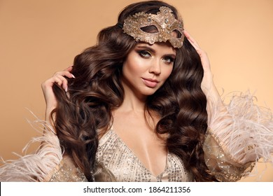 Beautiful brunette with Healthy wavy hair. Fashion Beauty Girl with carnival mask isolated on studio beige background. Glamour Makeup. Gold Jewelry. Hairstyle.