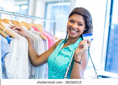 Beautiful brunette holding credit card in clothes store