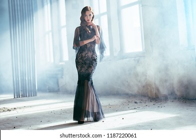 A beautiful brunette lady in ruins. Evening dress. Fashion, beauty.