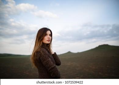 Beautiful brunette lady in soil field at sunset. Happy beautiful woman in meadow. Beautiful carefree woman in fields. Portrait of beautiful young woman.