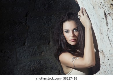 Beautiful brunette lady in the stony dungeon. Horizontal photo. Natural darkness and colors