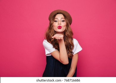 Beautiful brunette lady wearing like parisian blowing an air kiss to camera isolated over pink