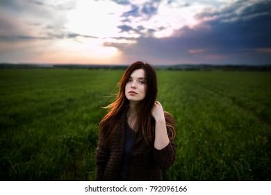 Beautiful brunette lady in wheat field at sunset. Happy beautiful woman in meadow. Beautiful brunette lady in wheat field at sunset