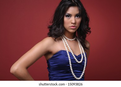Beautiful brunette Latino girl, posing in blue dress on red background.