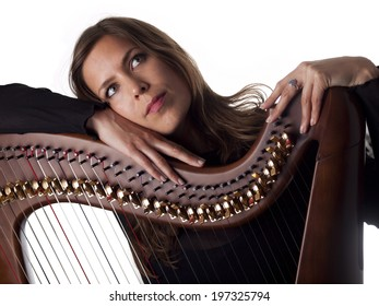 beautiful brunette leaning on her classical harp isolated over a white background