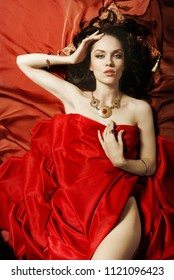 Beautiful brunette lies on a red bed