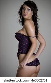 Beautiful brunette lingerie model pulling on pantie
