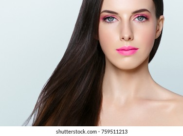 Beautiful brunette with long hair and pink lipstick and manicure nails. Studio shot.
