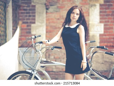 Beautiful brunette with long hair standing near a bike