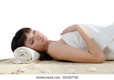 Beautiful brunette lying on a bamboo mat with her eyes closed. At the head is folded white towel and the next are small shells