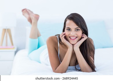 Beautiful brunette lying on bed looking at camera at home