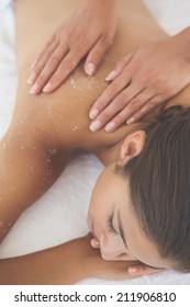 Beautiful brunette lying on massage table with salt scrub on back at the health spa