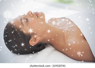 Beautiful brunette lying on massage table with salt scrub on chest against snow falling