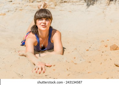 beautiful brunette lying on the warm sand on the beach