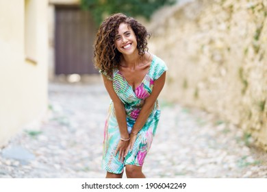 Beautiful brunette middle-aged woman in her 40s wearing spring colorful dress outdoors.