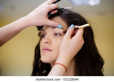 Beautiful brunette model in beauty salon on makeup
