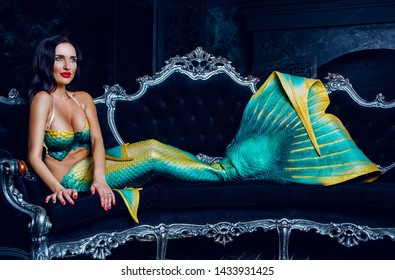 beautiful brunette model dressed as a mermaid , on the sofa