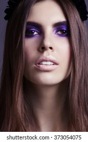 Beautiful brunette model in fashion clothes posing in studio. Wearing blue coat, black wreath. Portrait of young chic woman, perfect makeup. Fashionable clothes. Close up.