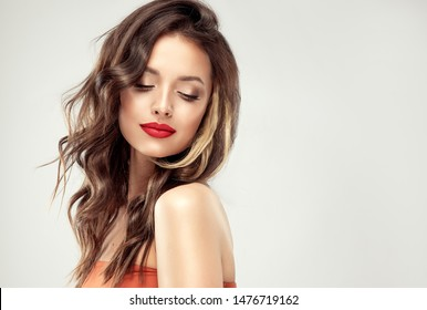 Beautiful  brunette model  girl  with long curly  hair . Hairstyle wavy curls . Red  lips and  nails manicure .    Fashion , beauty and make up portrait