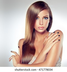 Beautiful brunette  model girl with long straight smooth hair . A woman in a silver dress and silver manicure on nails