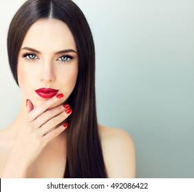Beautiful  brunette model girl with  long shine  hair .  Red lips and nails manicure .