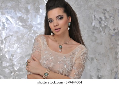 beautiful brunette model girl in long dress with white trees winter background