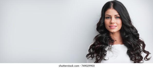 Beautiful brunette model with long curly black hair, studio shot