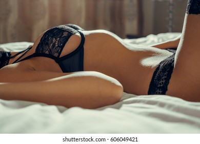Beautiful brunette model with perfect body lying on her bed in black lace lingerie. Shooting in a hotel room. Very sexy and sensual woman.