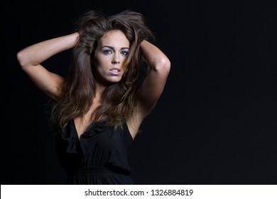 A beautiful brunette model posing in a studio environment