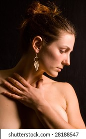 A beautiful brunette model in profile against black background, lit from the side