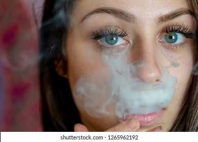 A beautiful brunette model smokes marijuana in the privacy of her own home
