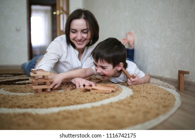 beautiful brunette mom playing with kid boy on the floor in wooden designer, casual lifestyle photo  in real life interior, hugging love family