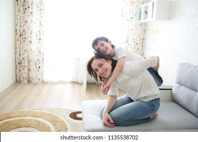 beautiful brunette mom and son hugging on the couch in a real interior, soft focus and light tone,
