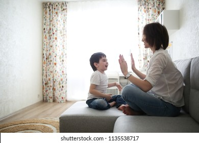 beautiful brunette mom and son hugging on sofa in real interior, soft focus