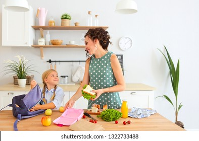 Beautiful brunette mother and her daughter packing healthy lunch and preparing school bag on the kitchen