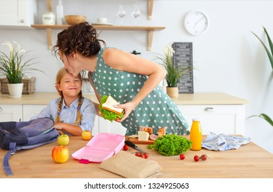 Beautiful brunette mother and her daughter packing healthy lunch and preparing school bag in the kitchen
