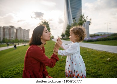 Beautiful brunette mother and her little daughter playing with flowers on the green lawn in the park. Skycraper background
