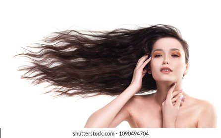 Beautiful brunette naked shoulders girl with flying horizontally sideways her long hair touches her face and neck. Nude make-up. Healthy smooth skin. Isolated on white background. Copy space.
