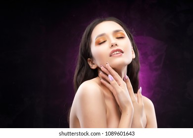 A beautiful brunette nude shoulders girl sensually touches the face and neck and smiles. Nude make-up. Healthy smooth skin. Purple-black background. Copy space. Commercial and advertising.
