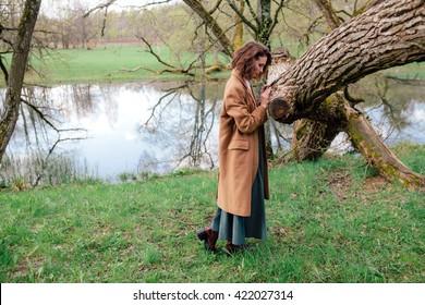 beautiful brunette on nature near a tree