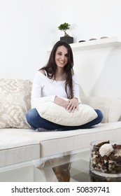 Beautiful brunette on the white sofa, smiling, with long hair.
