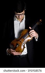 beautiful brunette plays the violin in the dark