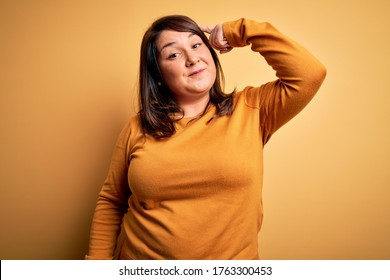 Beautiful brunette plus size woman wearing casual sweater over isolated yellow background Smiling pointing to head with one finger, great idea or thought, good memory