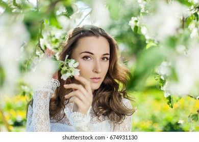 Beautiful brunette posing in blossoming apple-trees