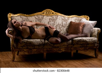 Beautiful brunette posing in lingerie on a couch
