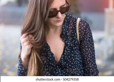 beautiful brunette posing on the street. fashion blogger wearing a stylish fall outfit - see through shirt and sunglasses. warm grade, street style
