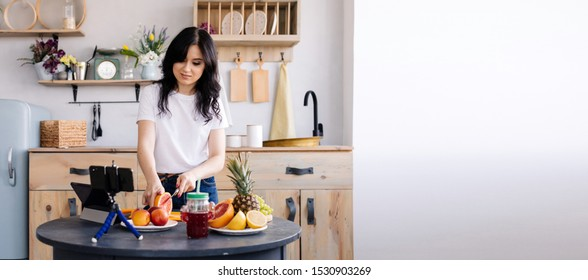 Beautiful brunette prepares fruit smoothie at home in the kitchen and removes the cooking process for her channel